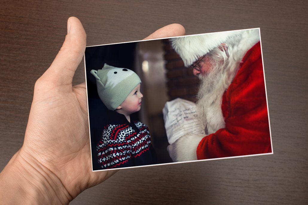 Postcard with a little boy on it who gets his present from Father Christmas.