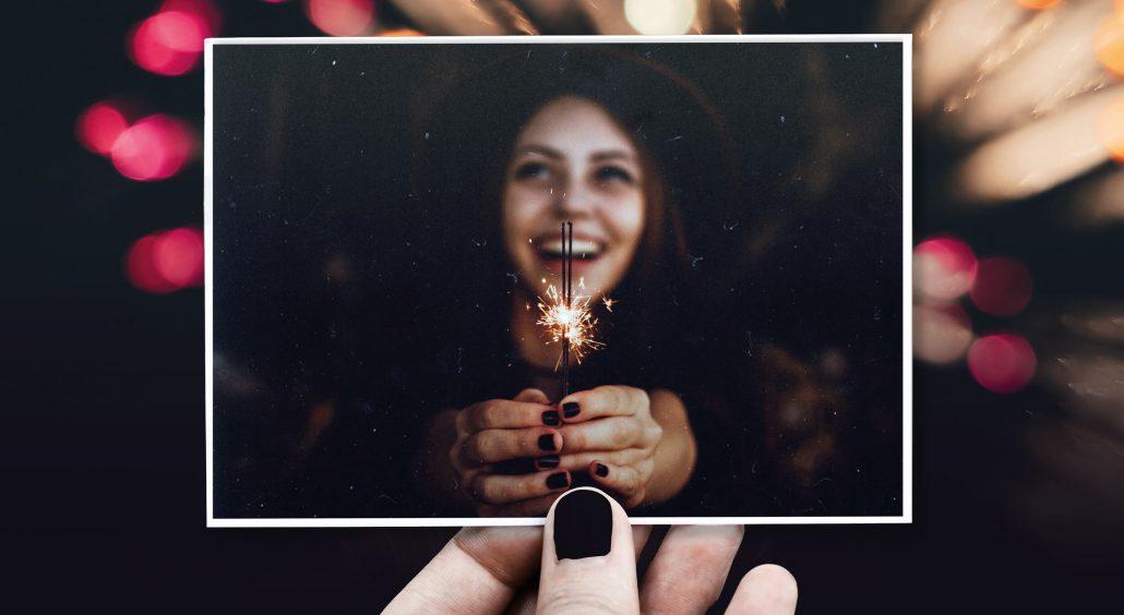 Neujahrskarte Lachende Frau hält Wunderkerze
