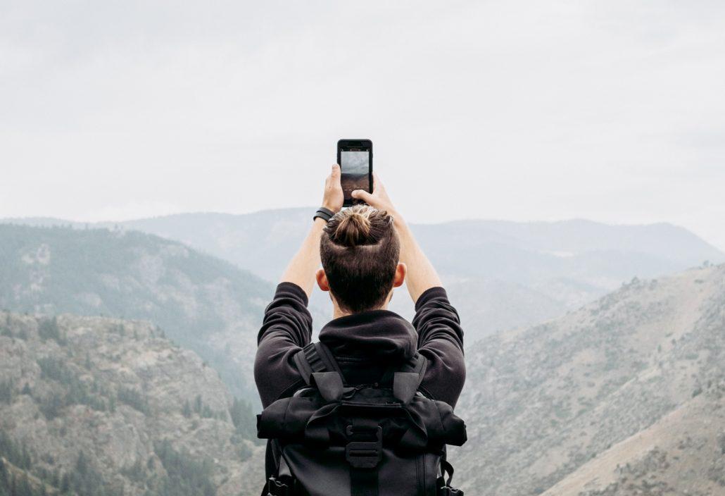 Mann nimmt Foto mit Smartphone auf