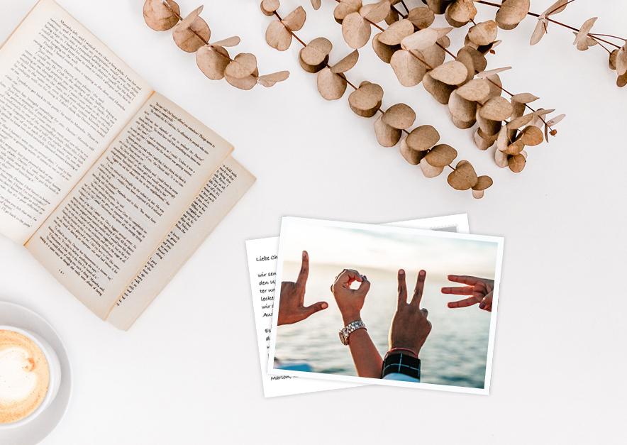 selbstgestaltete Postkarte mit Händen drauf die das Wort LOVE formen